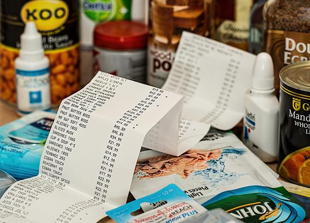 Grafika przedstawia paragon na tle zakupów różnego rodzaju.
